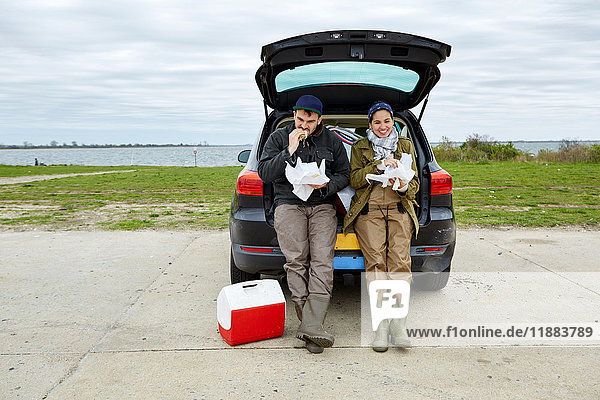 Young couple sitting in open car boot  eating food from paper