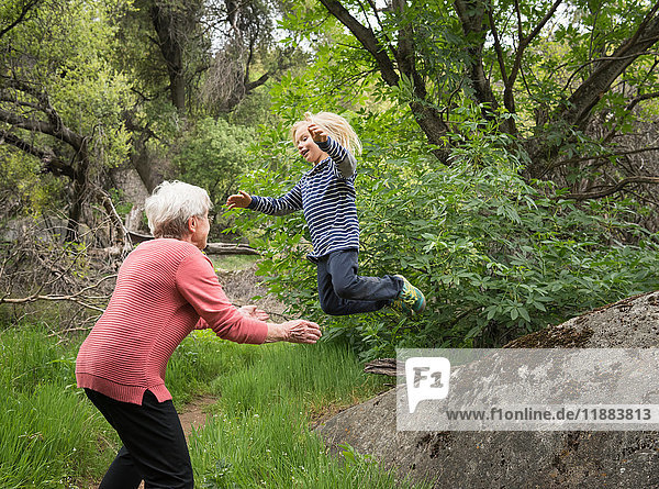 Grandson jumping off rock into grandmother's arms  Sequoia National Park  California  US