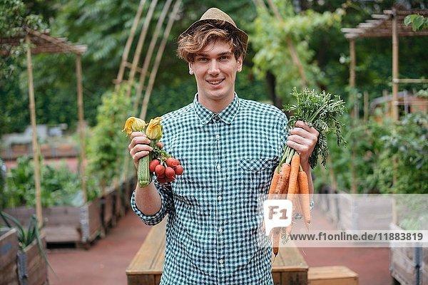 Mann im Garten mit lächelnden Möhrenbündeln