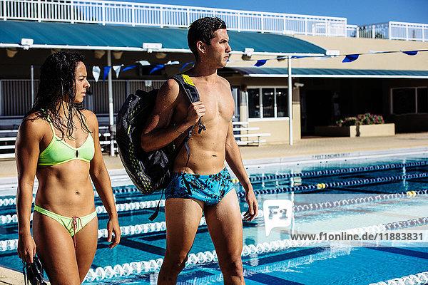 Swimmers walking by pool