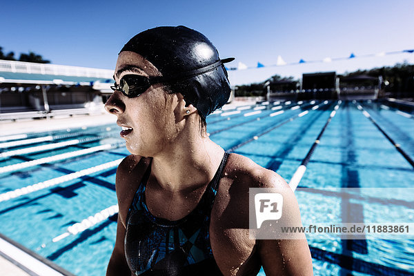 Swimmer in swimming cap and goggles catching breath by pool