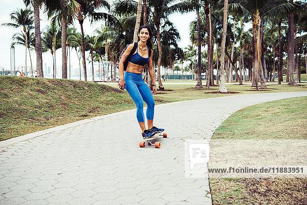 Junge Frau fährt mit dem Skateboard durch den Park  lächelnd  South Point Park  Miami Beach  Florida  USA