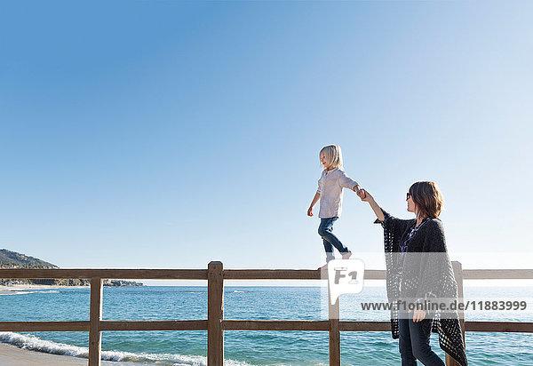 Kleiner Junge geht am Zaun entlang  hält die Hand der Mutter  Laguna Beach  Kalifornien  Vereinigte Staaten  Nordamerika
