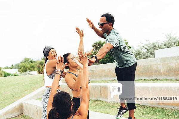 Drei Frauen feiern das Training mit ihrem Personal Trainer  South Point Park  Miami Beach  Florida  USA