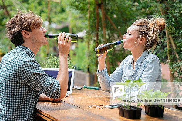Paar trinkt Bier im Garten