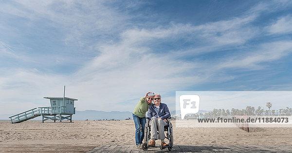 Älterer Mann im Rollstuhl mit Frau  die vom Strand aus auf ihn zeigt  Santa Monica  Kalifornien  USA
