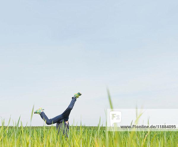 Boy cartwheeling in grass