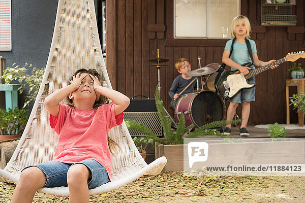 Girl in hanging chair  hands on head and children playing guitar and drums in band