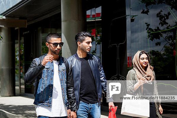 Drei Freunde gehen gemeinsam die Straße entlang