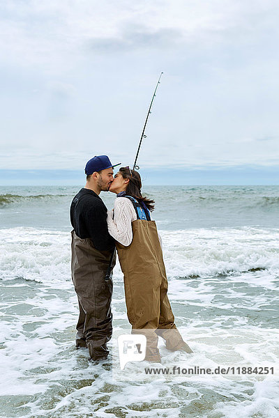 Young couple in waders kissing whilst sea fishing
