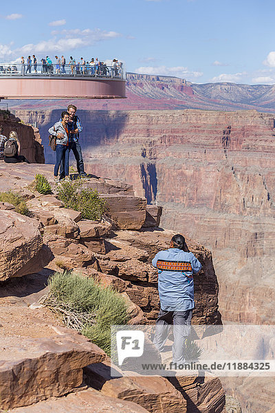 'A native american worker photographs tourists at the Skywalk Viewpoint over the West Grand Canyon natural landscape area in Arizona  a popular tourist attraction operated by the indigenous native American people; Arizona  United States of America'