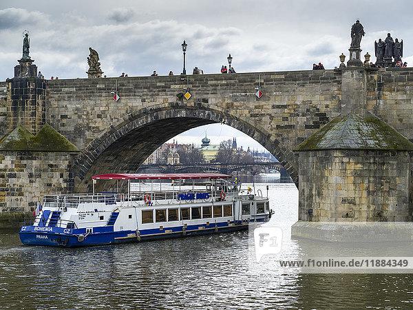 'A tour boat passing under Charles Bridge on the Vltava River; Prague  Czech Republic'
