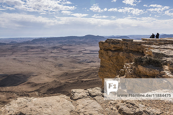 'People standing on a rock ridge looking out at the view of the rugged landscape  Ramon Nature Reserve; Mitzpe Ramon  South District  Israel'
