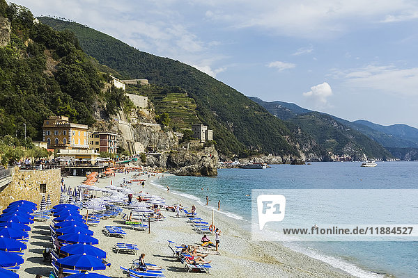 'Beach with blue canvas umbrellas at Monterosso village  part of the Cinque Terre hamlets on the Italian Riviera coastline; Monterosso  La Spezia  Italy'