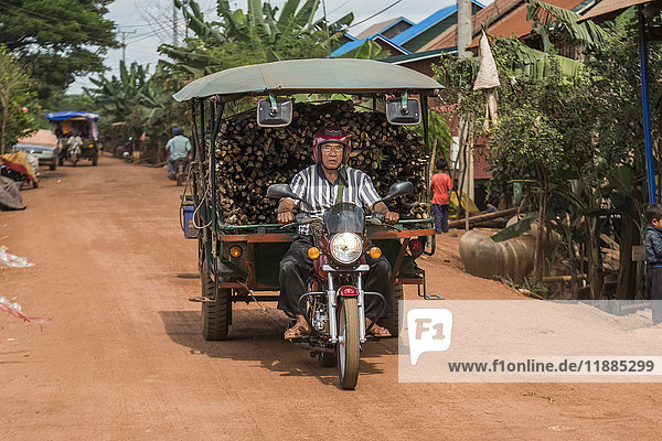 'A man rides a motorcycle pulling a cart full of cut wood; Siem Reap Province  Cambodia'