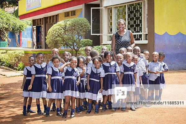 'Portrait of a teacher with her early education students at Treasures Christian Preschool; Kampala  Uganda' 'Portrait of a teacher with her early education students at Treasures Christian Preschool; Kampala, Uganda'