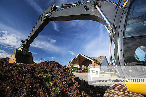 'An excavator digs up soil outside Lakemount Church; Grimsby  Ontario  Canada' 'An excavator digs up soil outside Lakemount Church; Grimsby, Ontario, Canada'