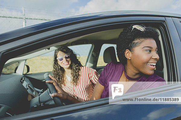 Lächelnde junge Frau schaut weg  während sie mit einer Freundin im Auto sitzt.