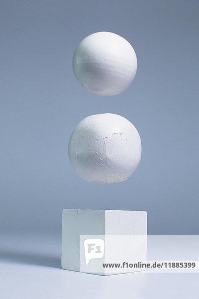 Weiße Kugeln schweben über Blockform vor grauem Hintergrund