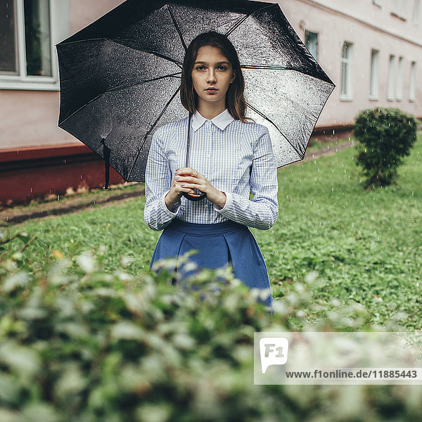 Porträt eines Teenagers  der bei Regen auf einer Wiese steht und einen Regenschirm hält.