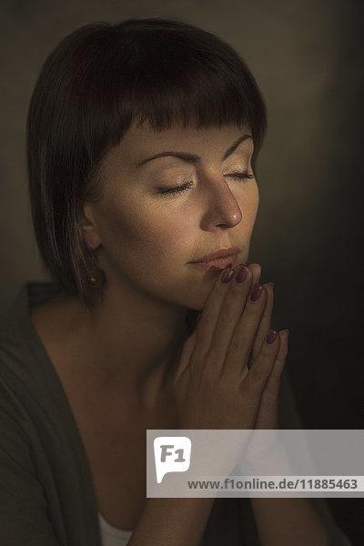 Mittlere erwachsene Frau mit geschlossenen Augen  die in Gebetsstellung vor grauem Hintergrund meditiert.