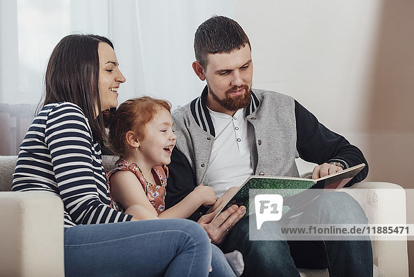 Parents reading book with daughter while sitting on sofa at home