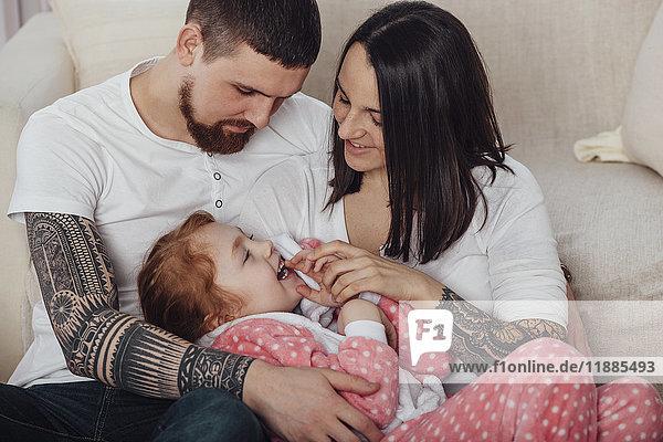 Lächelnde Eltern spielen mit der Tochter  während sie zu Hause auf dem Sofa sitzen.