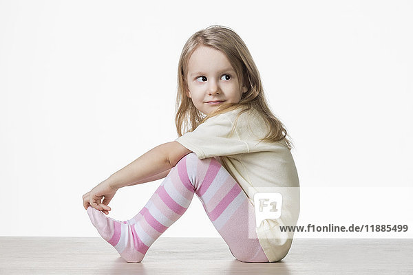 Seitenansicht des süßen Mädchens auf dem Boden vor weißem Hintergrund