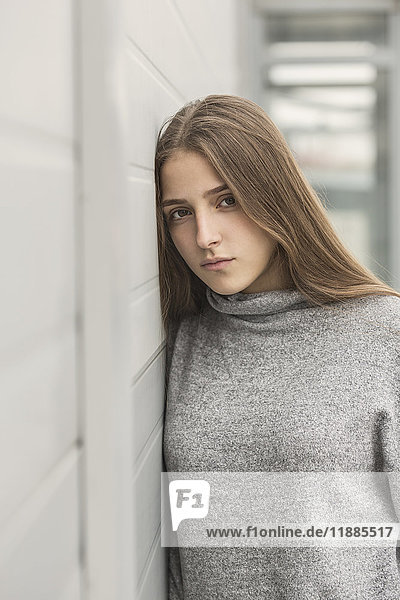 Porträt eines jungen Mädchens  das sich an die weiße Wand lehnt