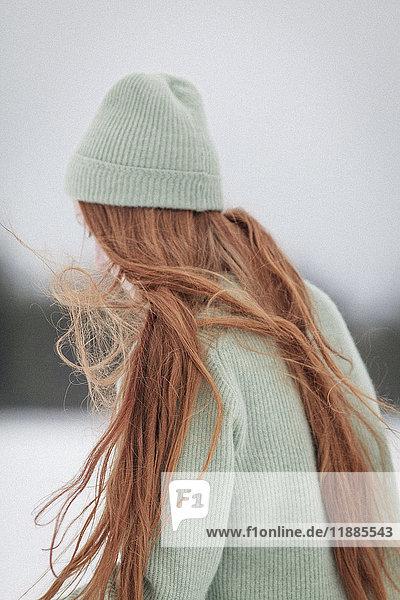 Junge Frau mit langen roten Haaren mit Strickmütze und Pullover gegen den klaren Himmel