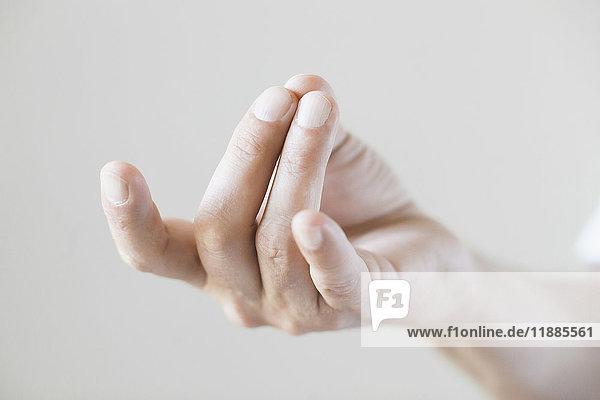 Abgeschnittenes Bild der Handbewegung vor weißem Hintergrund