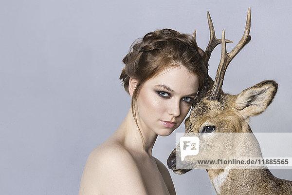 Porträt einer schönen Frau ohne Hemd mit Hirsch vor violettem Hintergrund