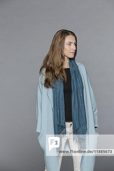 Junges Model mit Schal stehend mit Händen in Taschen vor grauem Hintergrund