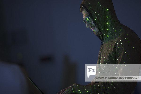 Grünes Licht über Computer-Hacker trägt Kapuzenshirt mit Laptop