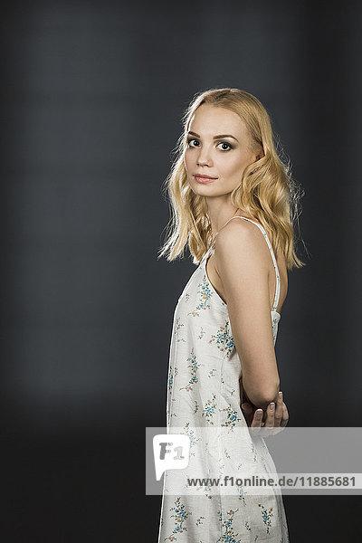 Seitenansicht Porträt einer blonden Frau vor schwarzem Hintergrund