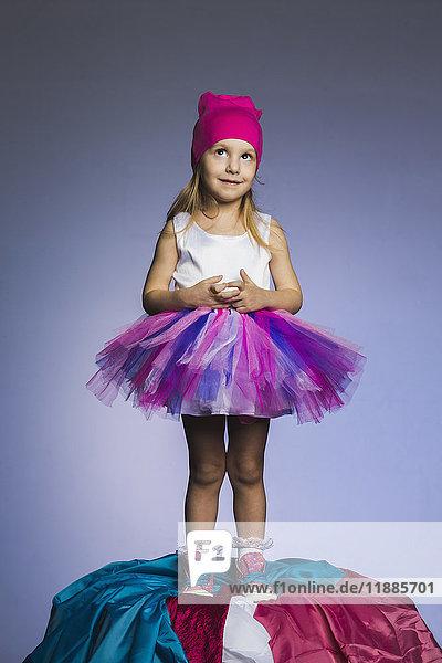 Süßes Mädchen mit Tüllrock und Strickmütze auf einem Stoffhaufen vor violettem Hintergrund.