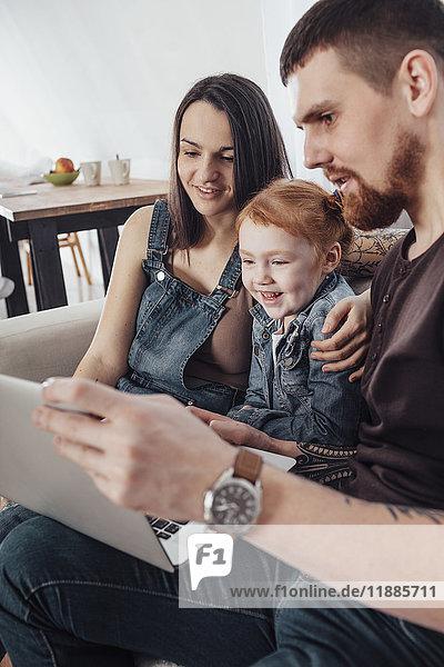 Lächelnde Eltern mit Tochter  die zu Hause auf dem Sofa sitzt und den Laptop anschaut
