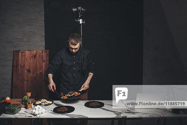 Chefkoch arrangiert Essen auf Marmortheke vor der Kulisse im Studio