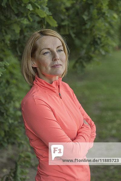 Nachdenkliche reife Frau mit gekreuzten Armen gegen Bäume im Park stehend