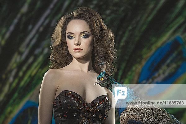 Porträt der schönen Frau von Pfau gegen Federn