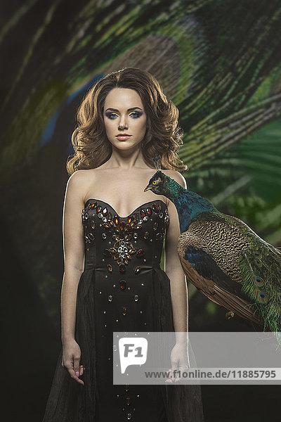 Porträt einer schönen Frau  die ein Kleid trägt  das an einem Pfau steht.