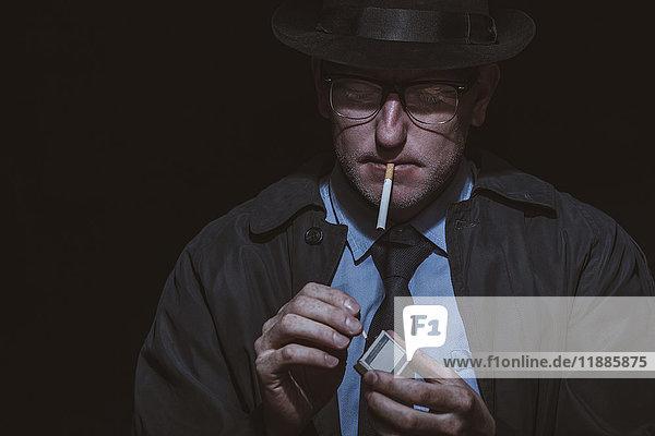 Junger Mann Beleuchtung Streichholz vor schwarzem Hintergrund