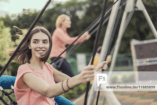 Lächelnde Frauen beim Schaukeln auf dem Spielplatz