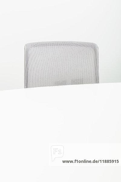 Grauer Bürostuhl mit Tisch vor weißem Hintergrund