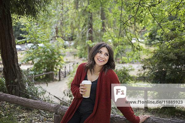 Glückliche Frau schaut weg  während sie Einwegglas im Park hält.
