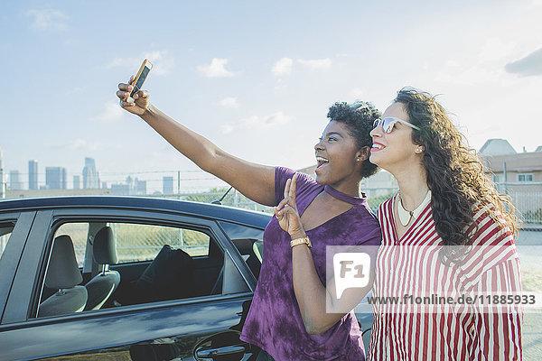 Glückliche junge Frau nimmt Selfie mit Freundin mit dem Auto gegen den Himmel  Los Angeles  Kalifornien  USA