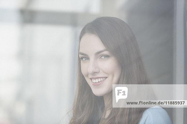 Porträt einer lächelnden jungen schönen Frau durch ein Glasfenster gesehen