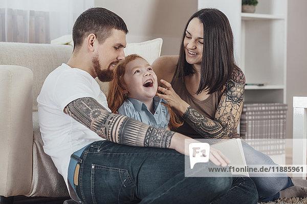 Fröhliche Eltern spielen mit der Tochter auf dem Sofa im Wohnzimmer zu Hause