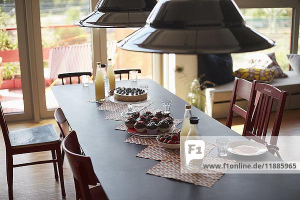 Hochwinkelansicht der Hängelampen  die über dem Essen hängen  das zu Hause auf dem Esstisch serviert wird.