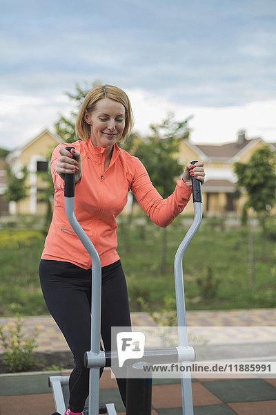 Lächelnde reife Frau mit Trainingsgeräten im Park gegen bewölkten Himmel